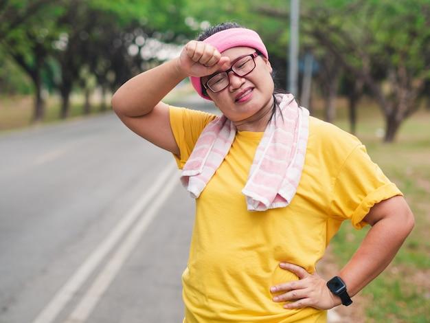 Mulher com sobrepeso se sentindo cansada enquanto corre no parque. conceito de perda de peso