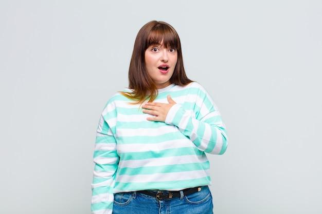 Mulher com sobrepeso se sentindo chocada e surpresa, sorrindo, levando a mão no coração, feliz por ser a única ou demonstrando gratidão