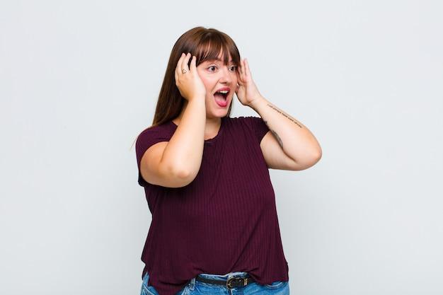 Mulher com sobrepeso se sentindo feliz, animada e surpresa, olhando para o lado com as duas mãos no rosto
