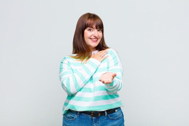 Mulher com sobrepeso se sentindo feliz e apaixonada, sorrindo com uma mão próxima ao coração e a outra esticada na frente