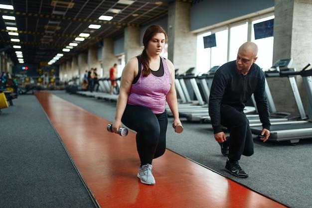 Mulher com sobrepeso segura halteres, exercício com treinador no clube desportivo, treino de ajuste com instrutor