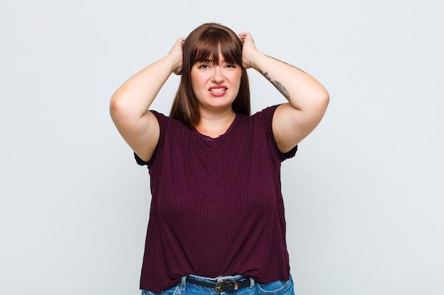 Mulher com sobrepeso sentindo-se estressada, preocupada, ansiosa ou com medo, com as mãos na cabeça, entrando em pânico com o erro