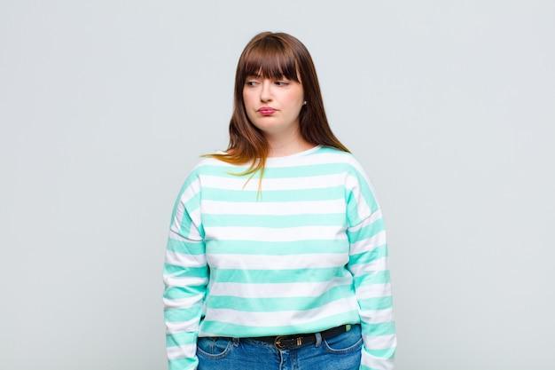Mulher com sobrepeso sentindo-se triste, chateada ou com raiva e olhando para o lado com uma atitude negativa, franzindo a testa em desacordo