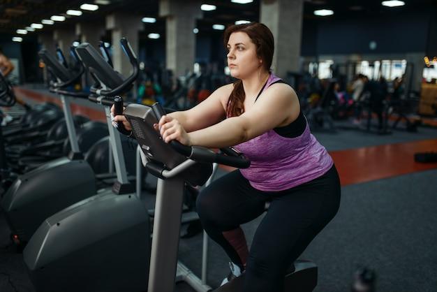 Mulher com sobrepeso treina na bicicleta ergométrica no ginásio, treinamento ativo. mulher obesa luta contra o excesso de peso, exercícios aeróbicos contra a obesidade, clube esportivo