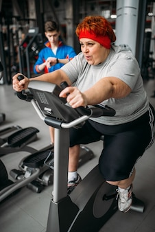 Mulher com sobrepeso, treino na bicicleta ergométrica no ginásio. queima de calorias, mulher obesa em clube desportivo, pessoas gordas
