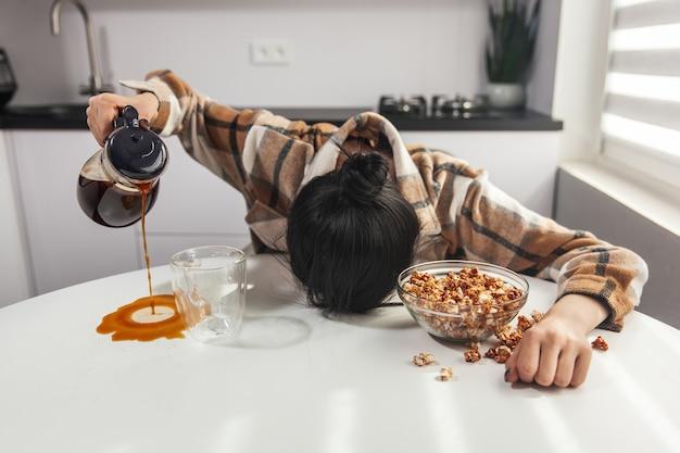 Mulher com sono adormece na mesa da cozinha durante o café da manhã e derrama café na caneca
