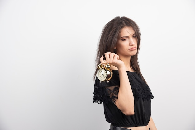 Mulher com sono carregando relógio