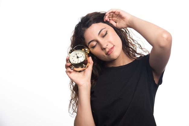 Mulher com sono com relógio segurando a cabeça no fundo branco