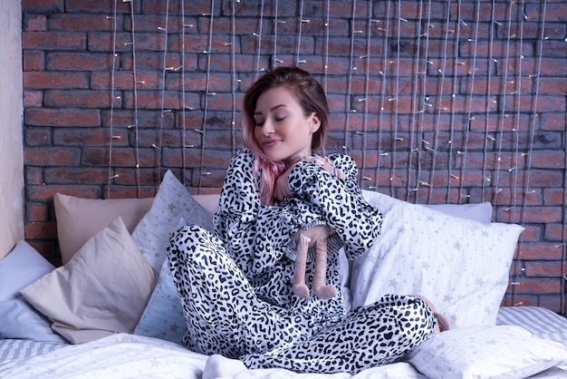 Mulher com sono de pijama de leopardo abraça seu rato tilda