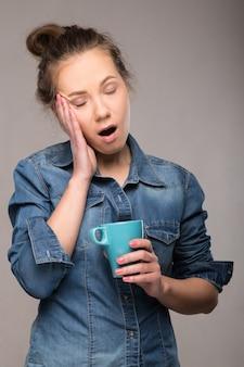 Mulher com sono em uma camisa jeans com uma xícara de café na mão