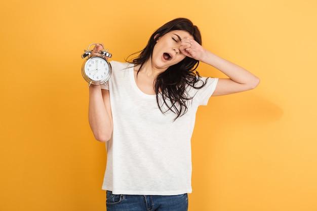 Mulher com sono isolada segurando o despertador bocejando.