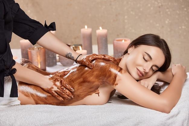 Mulher com sorriso adorável e olhos fechados deitada no spa e recebendo massagem corporal com chocolate