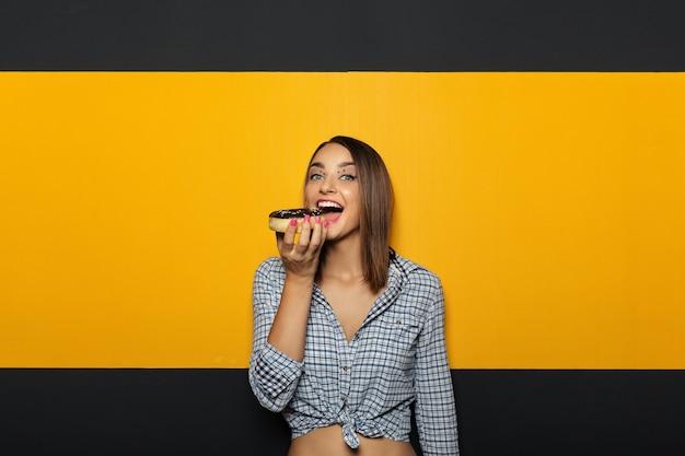 Mulher com sorriso brilhante branco comendo rosquinha saborosa.