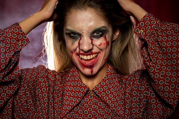 Mulher com sorriso de maquiagem de palhaço de halloween