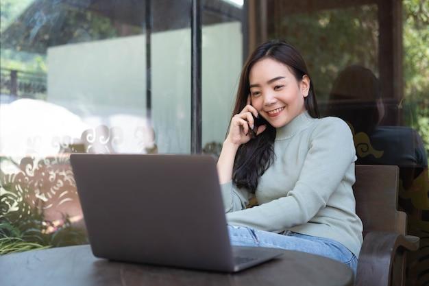 Mulher com sorriso fofo falando com o celular enquanto descansa no café.