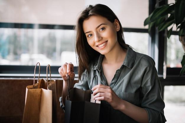 Mulher com sorriso lindo abrir sacolas. presente para descompactar o blogger