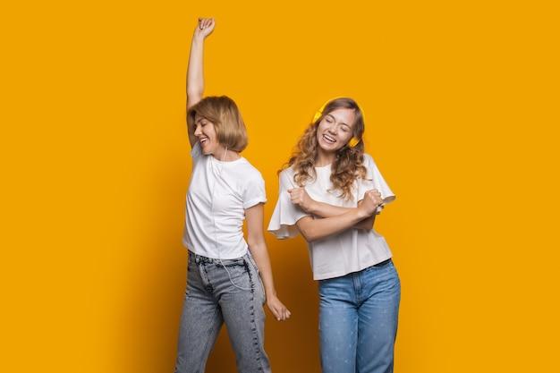 Mulher com sua amiga está ouvindo música e dançando
