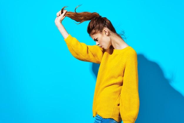 Mulher com suéter amarelo segurando cabelo azul fundo da moda