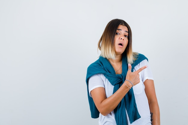 Mulher com suéter amarrado em camiseta branca, apontando para o canto superior direito e parecendo surpresa, vista frontal.