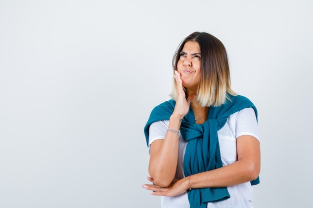 Mulher com suéter amarrado em t-shirt branca, apoiando o queixo na mão, olhando para cima e parecendo confusa, vista frontal.