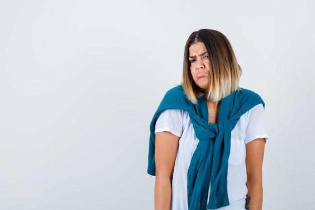 Mulher com suéter amarrado encolhendo os ombros, curvando o lábio inferior em uma camiseta branca e parecendo desapontada. vista frontal.