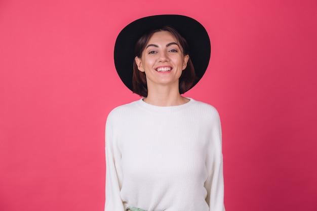 Mulher com suéter branco casual na parede rosa vermelha