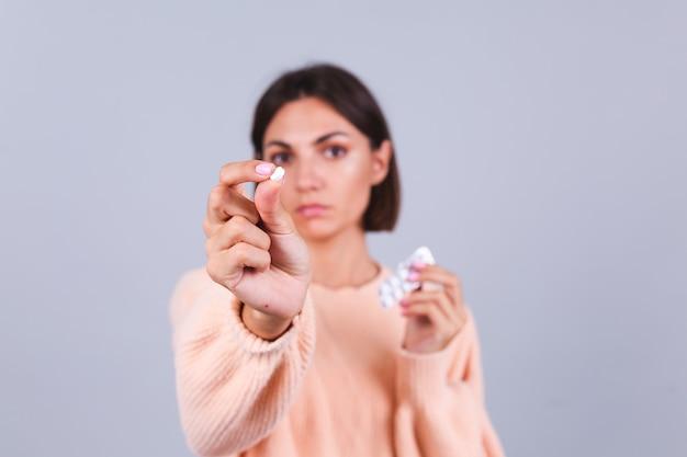 Mulher com suéter na parede cinza segurando uma caneca e comprimidos com uma expressão triste e infeliz no rosto