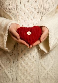 Mulher com suéter segurando um coração de malha vermelha