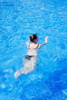 Mulher, com, swimsuit, natação, ligado, um, piscina água azul, tropicais, férias, feriado, conceito