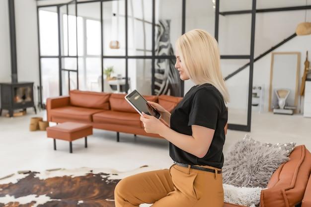 Mulher com tablet durante uma consulta online em sua sala de estar.