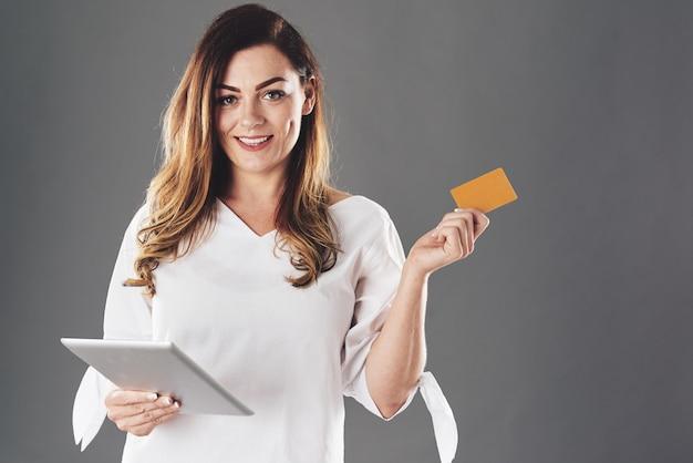 Mulher com tablet e cartão de crédito