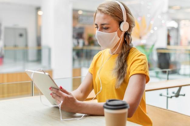 Mulher com tablet e fones de ouvido usando máscara