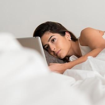 Mulher com tablet em close-up de cama