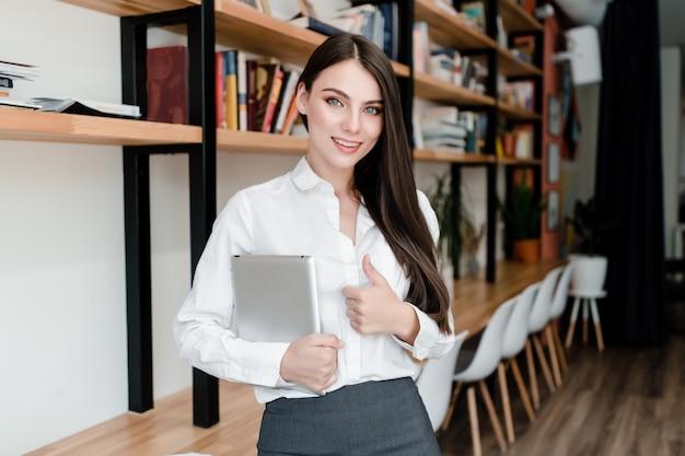Mulher com tablet no escritório mostra os polegares para cima