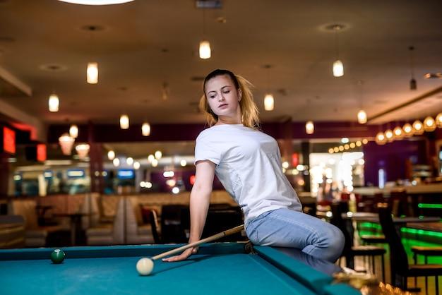 Mulher com taco sentada na mesa de bilhar e posando