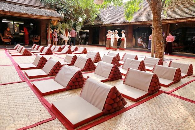 Mulher, com, tailandês, vestido tradicional, em, triangulo, travesseiro, ligado, madeira, casa tailandesa, chão