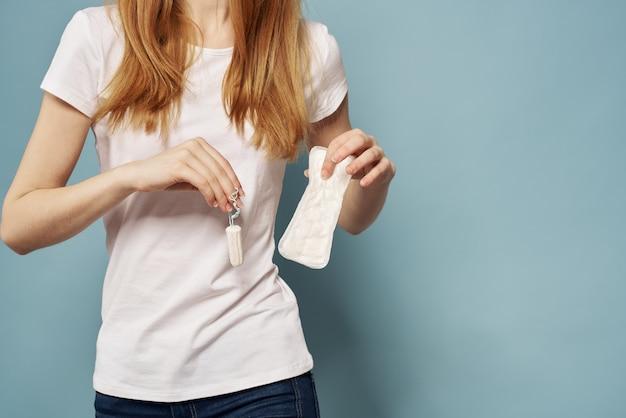 Mulher com tampão e absorvente na visão cortada de higiene das mãos e limpeza t-shirt branca azul.