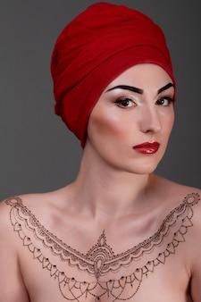 Mulher com tatuagem de hena e turbante vermelho