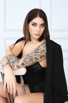 Mulher com tatuagem rosa em lingerie preta