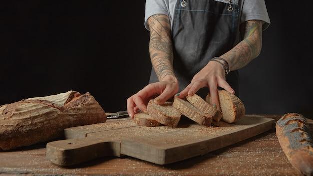 Mulher com tatuagens nas mãos com pão fresco na mesa de madeira