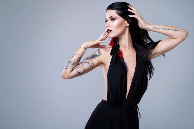Mulher com tatuagens usando vestido preto