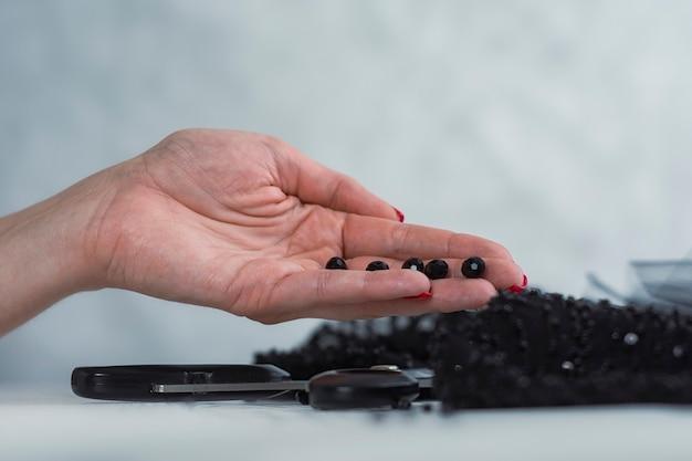 Mulher com tecido de cetim preto com tesoura em um fundo de madeira com miçangas.