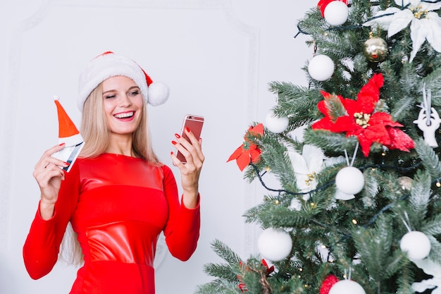 Mulher, com, telefone, e, cartão, perto, árvore natal