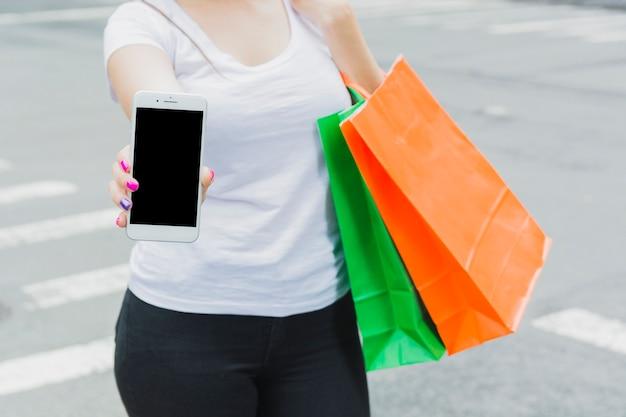 Mulher com telefone e sacolas coloridas