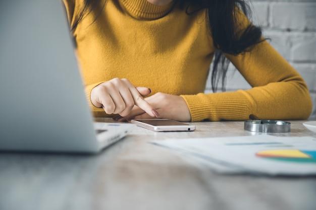 Mulher com telefone inteligente com o computador na mesa do escritório
