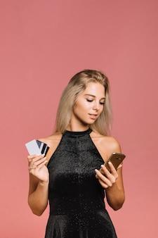 Mulher, com, telefone móvel, e, cartões crédito