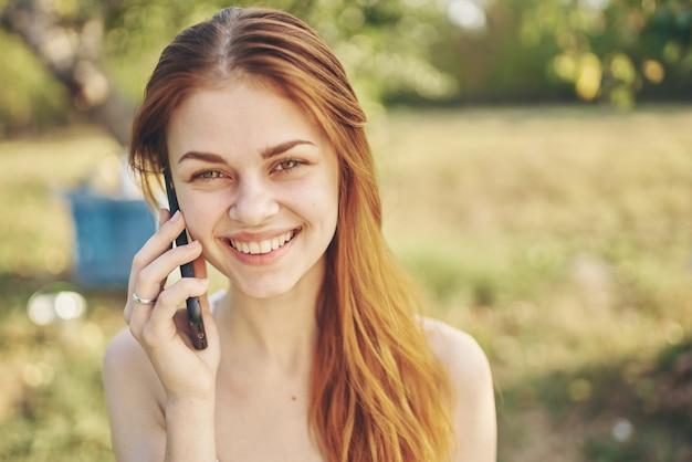 Mulher com telefone nas mãos, tecnologia de comunicação ao ar livre