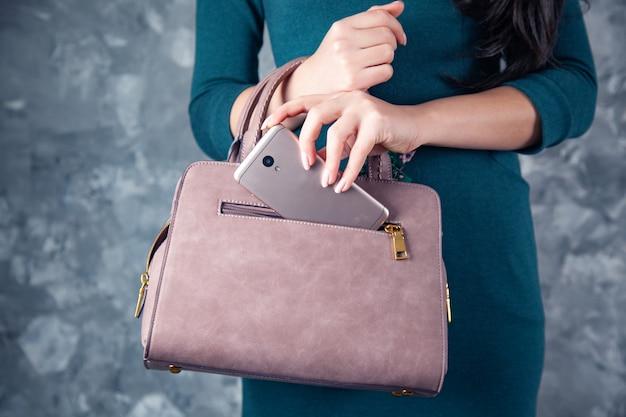 Mulher com telefone no bolso da bolsa em fundo cinza