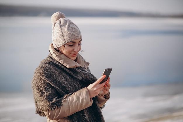Mulher com telefone no inverno perto do lago