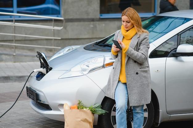 Mulher com telefone perto de um carro elétrico alugado. veículo carregado na estação de carregamento.